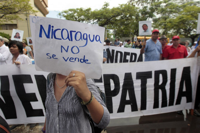 """An opponent of President Daniel Ortega's government holds a sign during a demonstration in front of the National Assembly Building in Managua June 13, 2013. Anti-government protesters chanted slogans against a proposed law that would grant the concession of an interoceanic canal to a Chinese company. The sign reads """"Nicaragua, Do not sell"""". REUTERS/Oswaldo Rivas (NICARAGUA)"""
