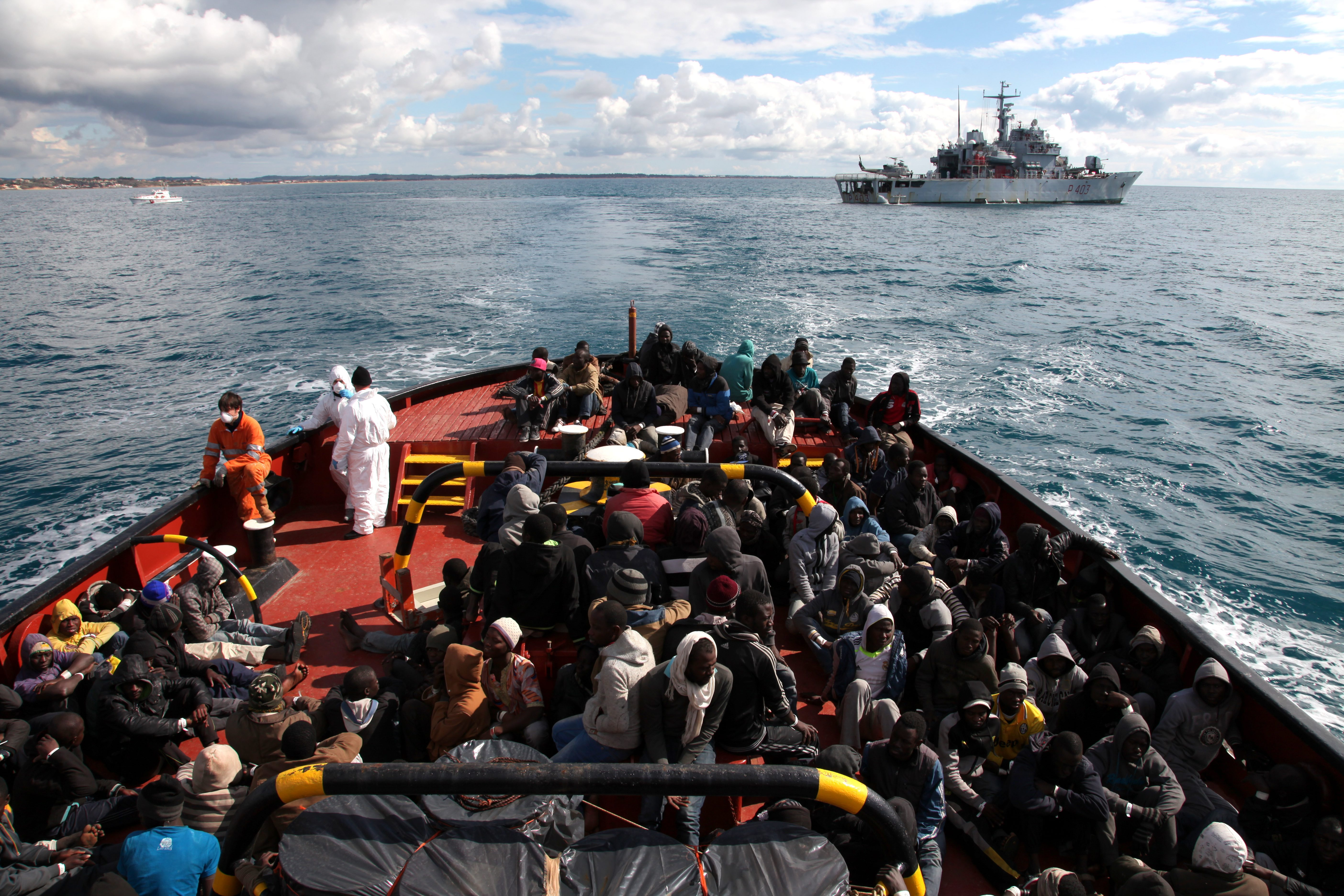 """Rescued refugees and migrants wait to disembark from the Italian Navy Ship """"Spica"""" onto a tugboat that will take them to the harbour of Pozzallo."""
